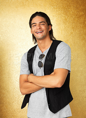 Buy stock photo Happy man with arms folded standing against gold background