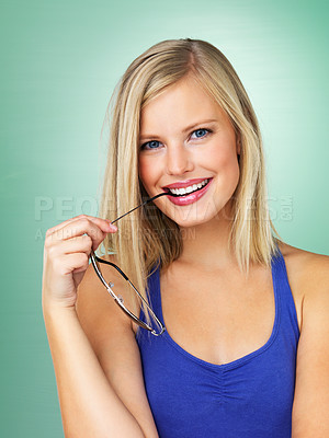 Buy stock photo Closeup of a pretty young woman with sunglasses in her mouth smiling against a fresh looking background