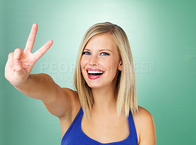 Buy stock photo Cheerful young woman showing victory sign