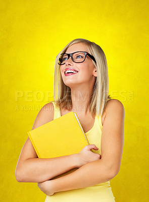 Buy stock photo Pretty woman holding book tightly against her