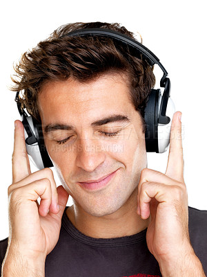 Buy stock photo Portrait of a relaxed young man listening to music on headphone against white background