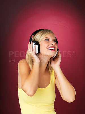 Buy stock photo Blonde woman looking up with headphones on against red background
