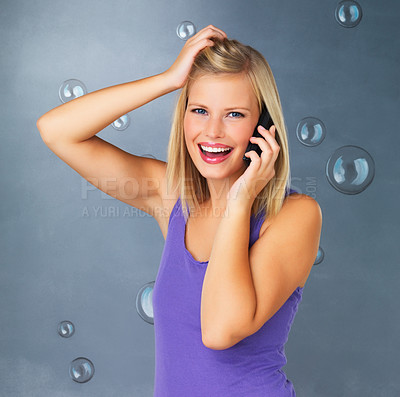 Buy stock photo Woman smiling with hand in hair while talking on cell phone