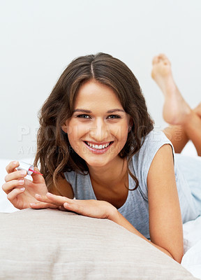 Buy stock photo Smiling girl painting her nails while on bed