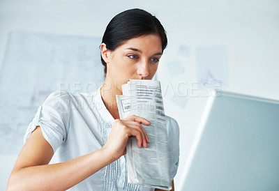 Buy stock photo Portrait of a smart young female business executive holding a newspaper and woking on laptop in office