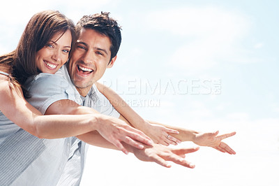Buy stock photo Portrait of a happy young man carrying a pretty woman on his back - Outdoor