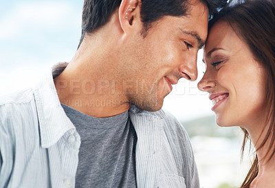 Buy stock photo Closeup portrait of a romantic young couple with their heads together
