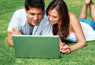 Buy stock photo Portrait of a cute young couple looking at the latop while lying on the ground - outdoor