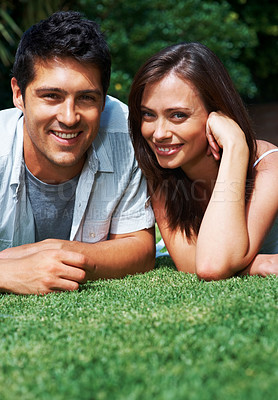 Buy stock photo Portrait of a cute young couple relaxing on the grass in park - Outdoor