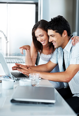 Buy stock photo A beautiful young couple using their laptop together in the kitchen at home