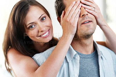 Buy stock photo Closeup portrait of a beautiful young woman covering her husband eyes to surprise him