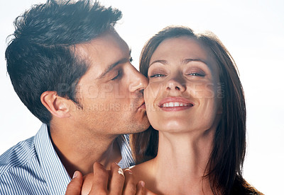 Buy stock photo Closeup portrait of a handsome young man kissing his girlfriend against bright background