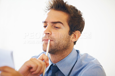 Buy stock photo Serious business man holding pencil and looking at the notepad