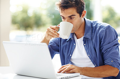 Buy stock photo Portrait of a young man drinking coffee while looking at his laptop at home in the morning - copyspace