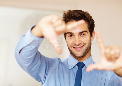 Buy stock photo Focus on a handsome young executive making a frame with his hands