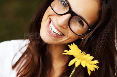 Buy stock photo Portrait of sweet young brunette in glasses with a yellow flower smiling confidently