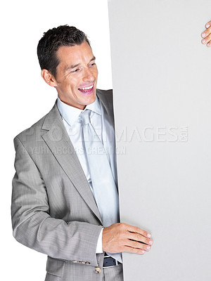Buy stock photo Portrait of a happy young male entrepreneur looking at blank billboard against white background
