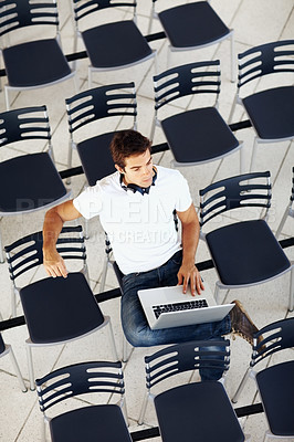 Buy stock photo Top view of young man sitting alone in a conference hall with a laptop and thinking
