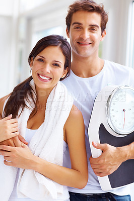 Buy stock photo Portrait of smiling young couple standing together with a weight scale in gym