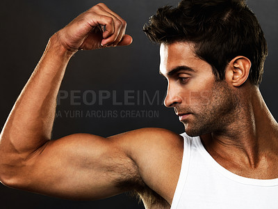 Buy stock photo Closeup of young man looking at his biceps on black background