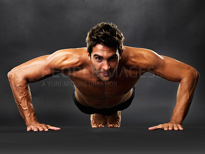 Buy stock photo Full length of young man doing pushups on black background