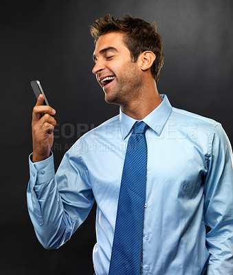 Buy stock photo Smiling business man holding his cellphone and reading a text message on black background