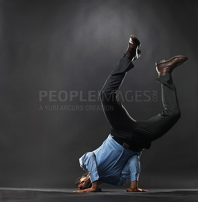 Buy stock photo Full length of business man trying to do handstand on black background