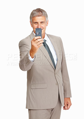 Buy stock photo Studio shot of a mature businessman taking a photograph with his mobile phone against a white background