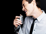 Young male star singer singing into old fashioned microphone