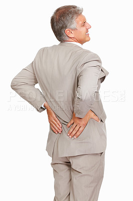 Buy stock photo Studio shot of a mature businessman suffering from backache against a white background