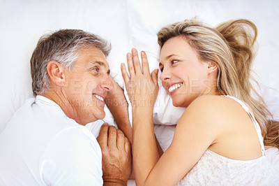 Buy stock photo Closeup of mature couple relaxing in bed and smiling