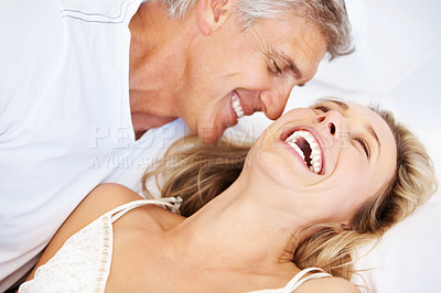 Buy stock photo Portrait of mature couple having happy time together lying in bed at home