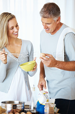 Buy stock photo Man holding an egg to prepare batter with woman in kitchen at home