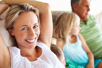 Buy stock photo Beautiful mature woman smiling at you while relaxing next to her family on their couch - copyspace