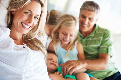Buy stock photo Mature woman relaxing at home with family in background