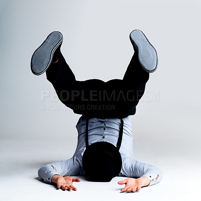 Buy stock photo Portrait of a crazy young guy lying on floor in weird position against grey background