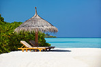 Relax on the beach - Seashore with deck chairs under umbrella