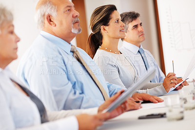 Buy stock photo Four business colleagues sitting in row on business presentation and paying attention