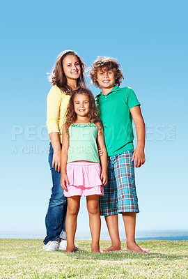 Buy stock photo Portrait of happy little children standing on grass against clear blue sky