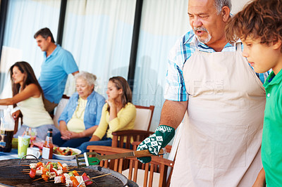 Buy stock photo Portrait of senior man and grandson barbecuing with family in the background