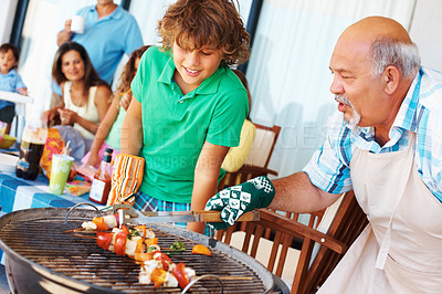 Buy stock photo Grandfather showing his grandson the perfect way to barbecue while the family is enjoying a day together
