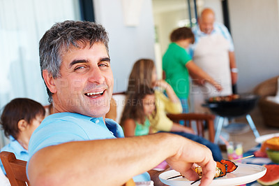 Buy stock photo Portrait of an mature man barbecuing with family in the background at the weekend