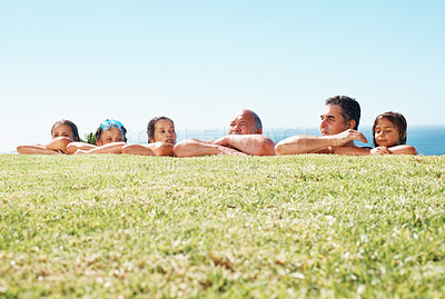 Buy stock photo Happy family in a row resting head in hands outdoors - copyspace