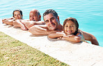 Family resting on the edge of swimming pool