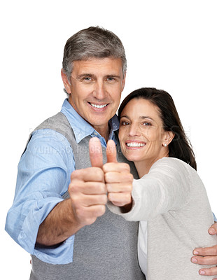 Buy stock photo Portrait of a happy middle aged couple gesturing thumbs up sign against white background
