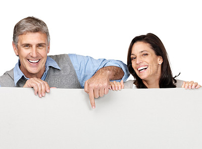Buy stock photo Portrait of a happy mature couple pointing at blank billboard against white background