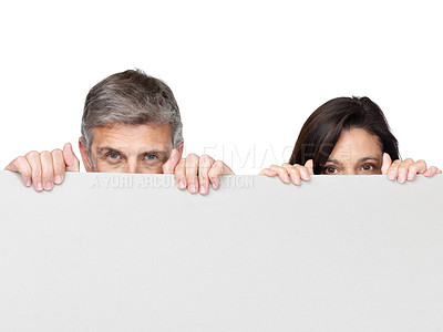 Buy stock photo Portrait of a Mature couple peeping over a blank board against white background