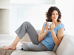 Happy young woman with coffee on couch