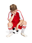 Defeat - Upset young boy sitting on the soccer ball