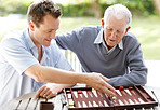 Father and son playing backgammon in a park
